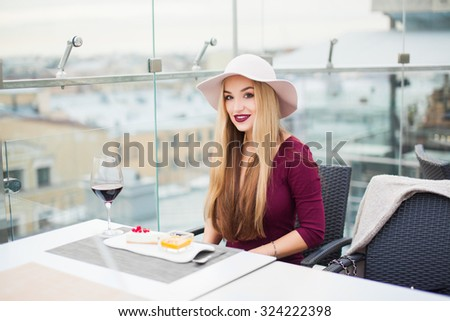 Close-up sensual woman sitting in a cafe with a great view of the city in Europe,try tasty panakota desert,long blonde hair,elegant outfit,fantastic woman,red vine.hat,lounge atmosphere,rest time    - stock photo