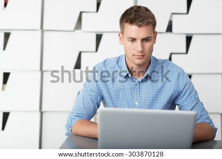 Close up Serious Handsome Young Businessman Using his Laptop Computer on Top of the Table Inside the Office - stock photo