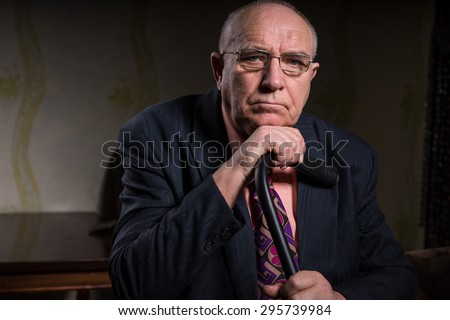Close up Serious Middle Aged Bald Businessman in Formal Attire, Holding his Cane and Looking at the Camera While Leaning his Chin on his Hand. - stock photo
