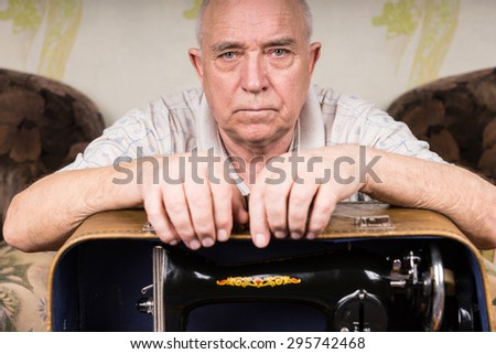 Close up Serious Old Tailor Guy Leaning on his Sewing Machine in a Carrying Case Inside his House and Looking Straight at the Camera. - stock photo