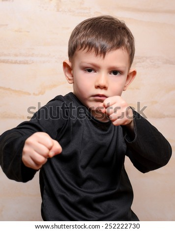 Close up Serious White Fighter Male Kid in Black Clothing Posing with Closed Fists While Looking at the Camera. - stock photo