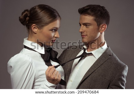 Close Up Serious Young Couple Face to Face Portrait. Isolated on Gray Background. - stock photo