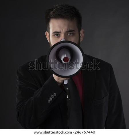 Close up Serious Young Man in Black Formal Wear Holding Megaphone While Looking at the Camera. Captured on Gray Background - stock photo