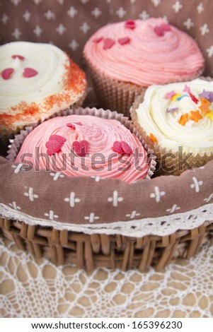 Close up set of colorful cupcakes in basket on retro white tablecloth, wooden background, brown table.Chocolate Cupcake, strawberry pink, bright white vanilla. Cafe, restaurant, sweets, cakes.