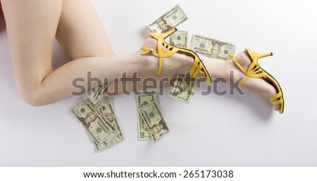 Close up Sexy Flawless Woman Legs in Yellow Shows Lying on the Floor with Plenty of US Dollars, Isolated on White Background. - stock photo