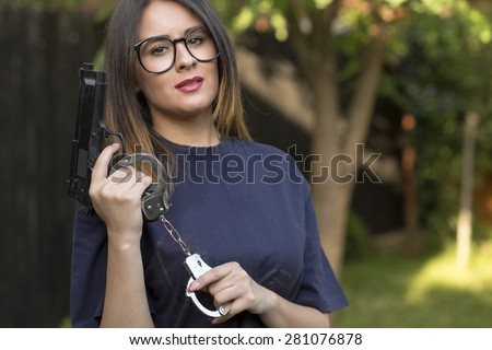 Close up Sexy Girl in T-Shirt Holding a Hand Gun and a pair of handcuffs - stock photo