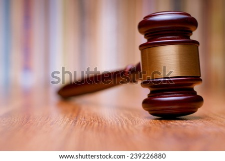 Close up Shiny Wooden Gavel with Gold Plate on Wooden Table. Emphasizing Authority and Right to Act Symbol. - stock photo