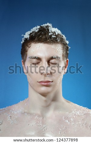 Close up shoot of an young frozen man with ice on a hair - stock photo