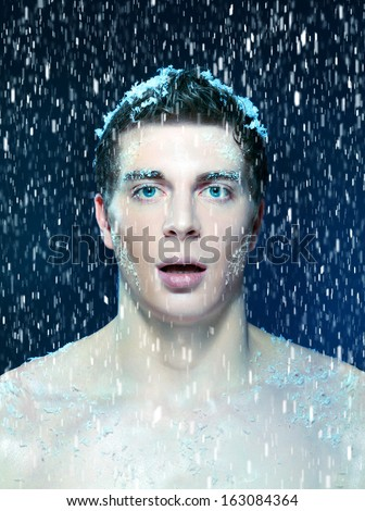 Close up shoot of an young frozen man with snow on a hair, beard and eyelashes under the snowing by snow - stock photo