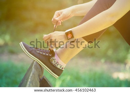 Close up shoot of female tying shoelaces and wearing watchband touchscreen smart watch with blank screen outdoors. Healthy lifestyle and new technology concepts.