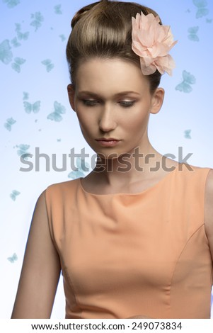 close-up shoot of lovely lady posing with elegant hair-style, pink flower on head and wearing simple orange dress. - stock photo