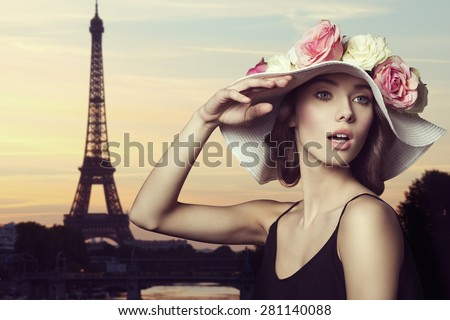 close-up shoot of very pretty brunette female with big floral hat with some colorful roses and stylish make-up. Posing with surprised expression . she is in paris - stock photo