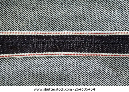 close up shot inside of raw denim dark wash indigo blue jeans texture background show redline selvage - stock photo