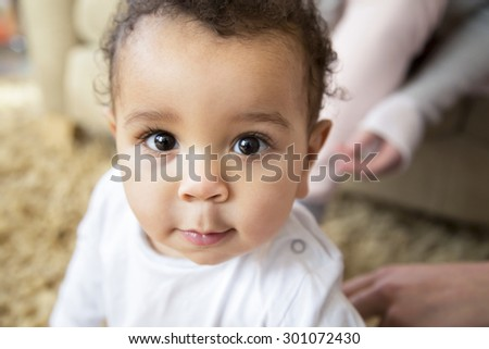 Close up shot of a baby smiling at the camera. He is sitting on a rug in his home with his mothers in the background - stock photo