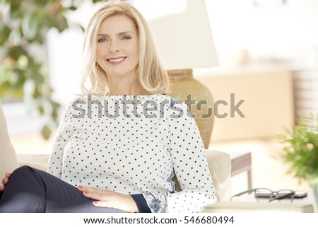 Close-up shot of a beautiful blond elderly woman looking at camera and smiling while sitting on couch at home.