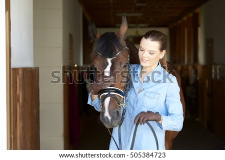 Close-up shot of a beautiful young woman taking care her horse at horse stable.
