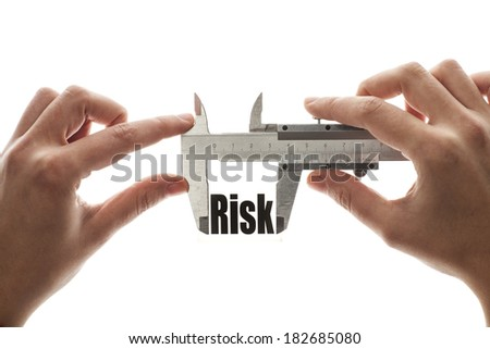 """Close up shot of a caliper measuring the word """"Risk"""" - stock photo"""