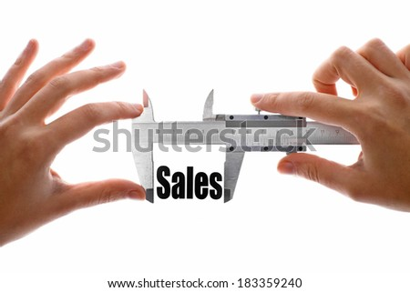 "Close up shot of a caliper measuring the word ""Sales"". - stock photo"