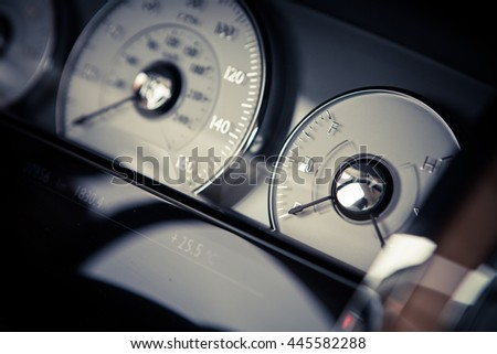 Close up shot of a car's dashboard with the fuel gauge. - stock photo