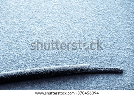 Close-up shot of a car's windscreen wiper covered in snow - stock photo
