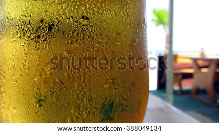 Close-up shot of a cold wet beer glass with condensation on it, against the tropical background, palm, beach and wooden beach bar table. - stock photo