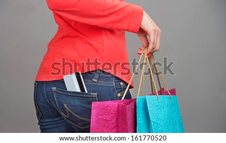 Close-up shot of a credit card in pants pocket and a female hand holding shopping paper bags