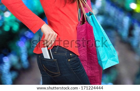 Close-up shot of a credit card in pants pocket and a female hand holding shopping paper bags, city lights background