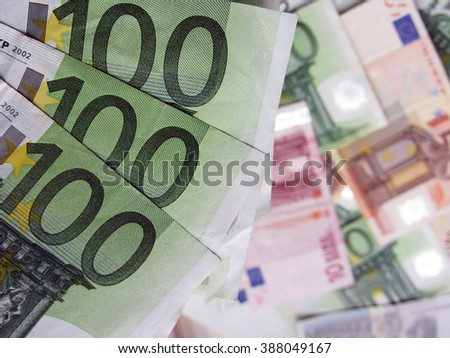Close up shot of a few 100-Euro money notes with a pile of cash in background.
