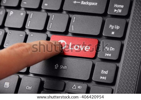 Close up shot of a finger clicking the LOVE button on a laptop keyboard
