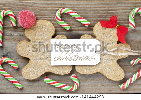 Close-up shot of a gingerbread couple surrounded by candy canes and a Merry Christmas tag over wooden plank.
