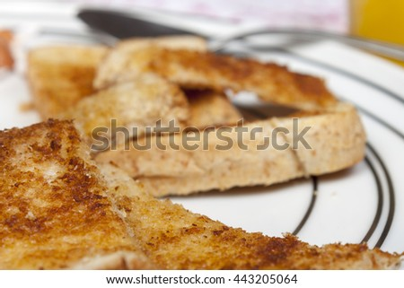 Close up shot of a golden brown buttered slice of toast on a white pattened plate - stock photo
