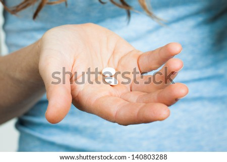 Close-up shot of a hand holding two white pills. - stock photo