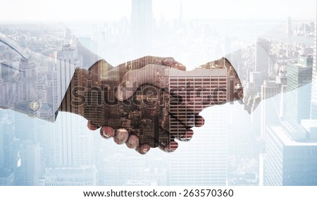 Close-up shot of a handshake against city skyline - stock photo