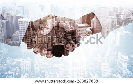 Close-up shot of a handshake against high angle view of city - stock photo