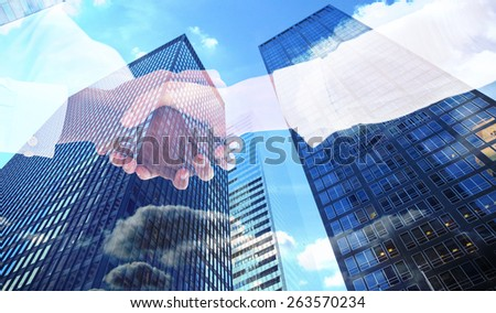 Close-up shot of a handshake against skyscraper - stock photo