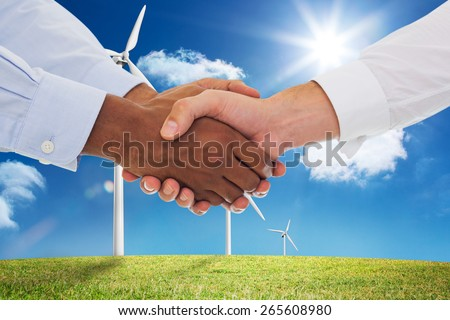 Close-up shot of a handshake in office against digital landscape with three wind turbines - stock photo