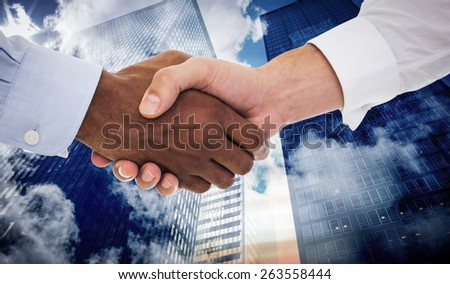 Close-up shot of a handshake in office against low angle view of skyscrapers - stock photo