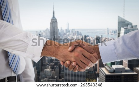 Close-up shot of a handshake in office against new york - stock photo