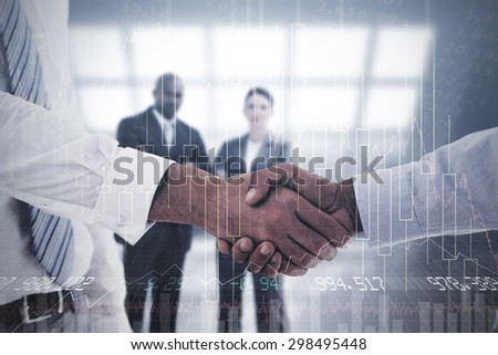 Close-up shot of a handshake in office against stocks and shares - stock photo
