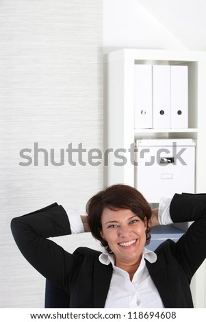 Close up shot of a happy businesswoman holding her back head - stock photo