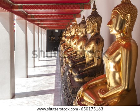 Close up shot of a line of golden Buddha statues receding into the distance at Wat Pho in Bangkok,Thailand. A Buddhist temple directly south of the Grand Palace.