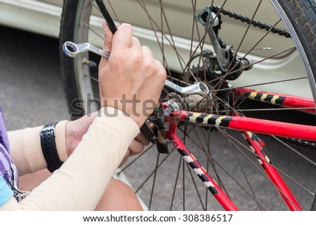 close up shot of a man (only hand) fixing his bicycle