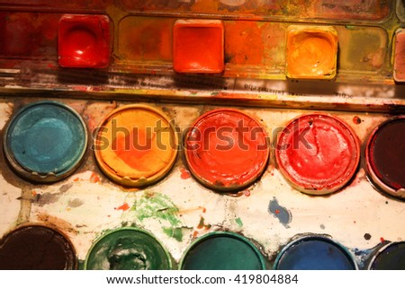 Close up shot of a messy watercolor palette with colorful splatters and stains - stock photo