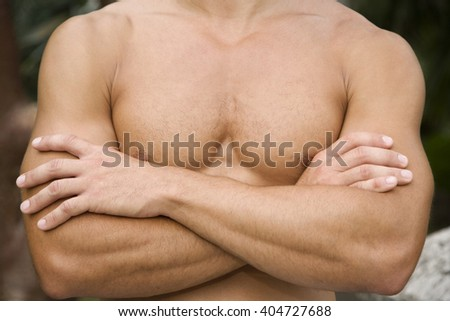 Close up shot of a muscular man's chest and arms.