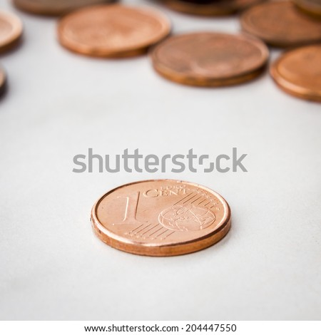 Close up shot of a one euro cent coin isolated on a white background and some pile coins. - stock photo