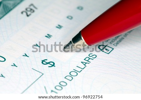 Close-up shot of a pen writing on a cheque. Shallow focus. - stock photo