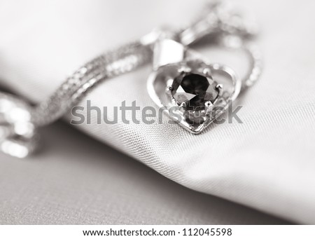 Close up shot of a pendent on satin cloth - stock photo