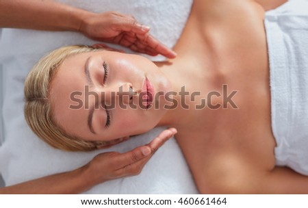 Close up shot of a relaxed woman on massage table receiving beauty treatment at dayspa