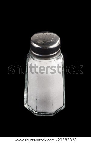 Close-up shot of a salt shaker on black background - stock photo