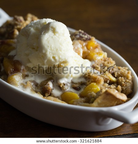 Close up shot of a serving of peach cobbler with a scoop of vanilla ice cream.  - stock photo